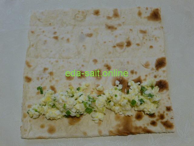 Положить на лаваш начинку из сыра и яиц