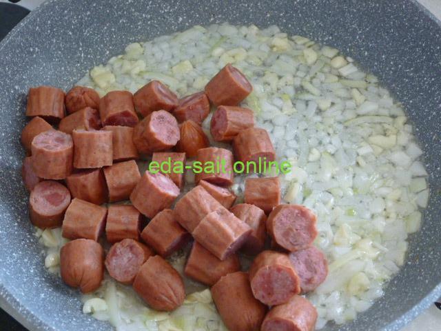 Выложить колбаски к луку и чесноку