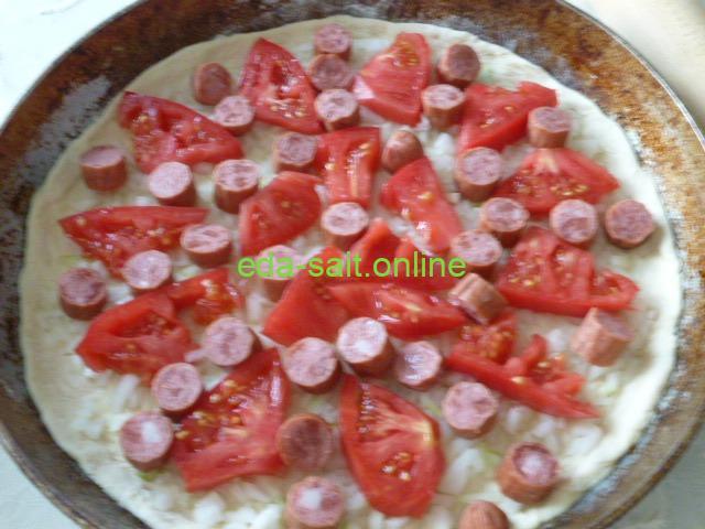 Выложить в пиццу колбаски и помидоры
